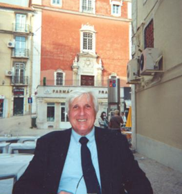 Frank Dutra at an outdoor restaurant in front of a couple buildings