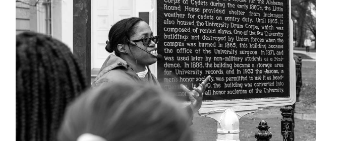 """Women in front of a The Little Round House sign with caption """"Author discussing the Little Round House marker on a February 2020 Hallowed Grounds tour. (Photo by author)"""""""