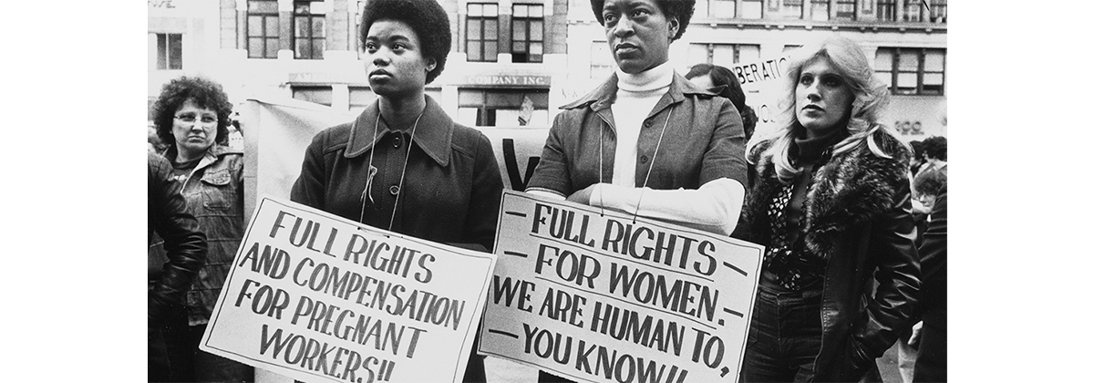 "Image of four women, two with signs that read ""Full rights and compensation for pregnant workers!!"" and another says ""Full rights for women. We are human to, you know!!"""
