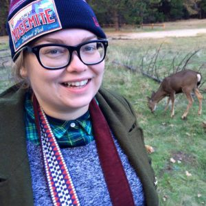 Nicky Rehnberg in a park with a deer in the background