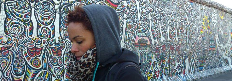A young, ethnic women walks along a muralled wall. She is one of the faces of a new, multicultural Germany.