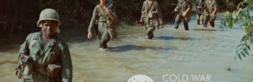 6 people in camoflauge uniform wading in a river. UCSB Cold War Working Group