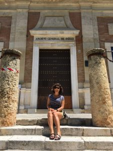 Andreina Soto sitting on the steps of Archivo General De Indias